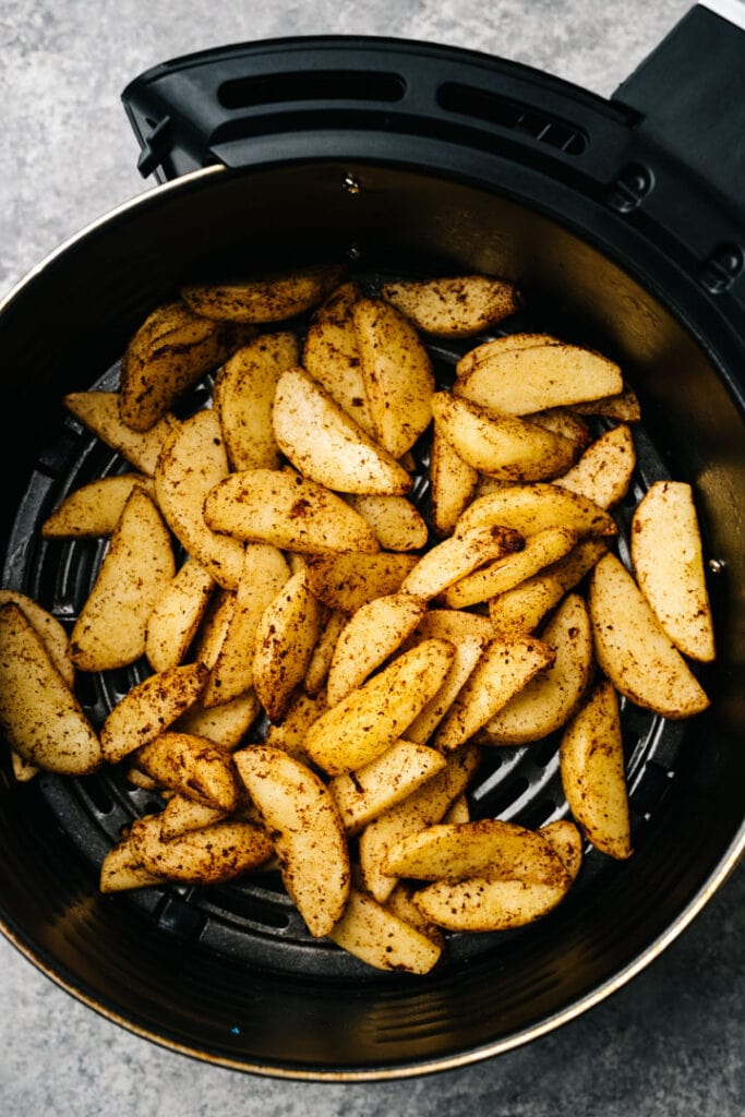 Fried apples in the basket of an air fryer.