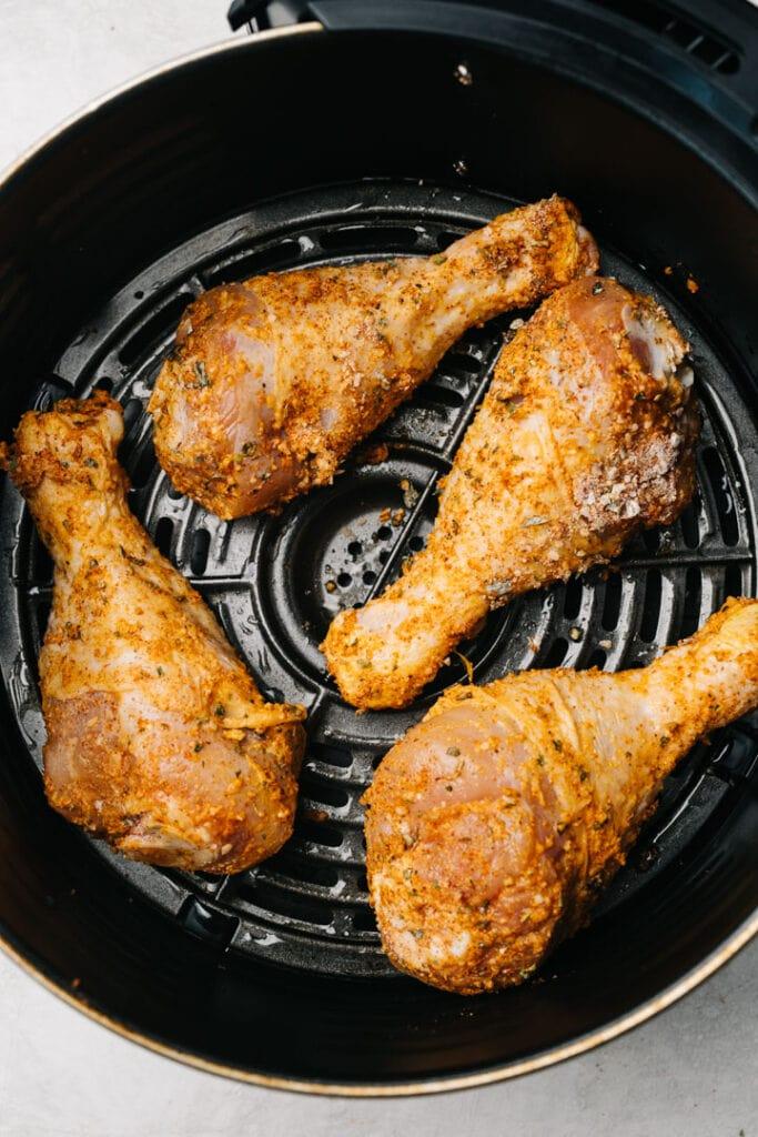 Chicken drumsticks halfway through cooking in the basket of an air fryer.