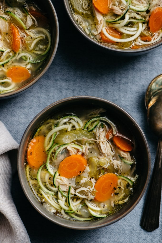 Three bowls of chicken zoodle soup on a blue linen tablecloth with a tan linen napkin and vintage soup spoons on the side.