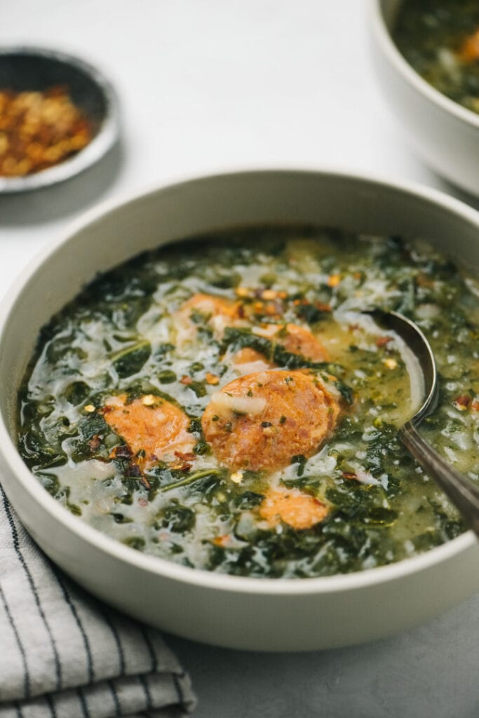 Side view, a bowl of caldo verde sausage and kale soup on a concrete background with chili flakes in the background.