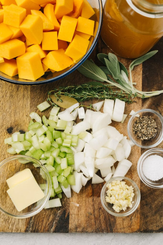 The ingredients for homemade butternut squash soup arranged on a wood cutting board.