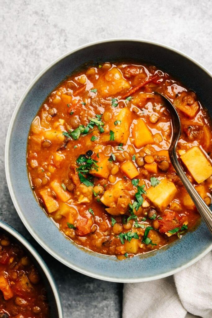 Instant pot lentil soup in a blue bowl on a concrete background.