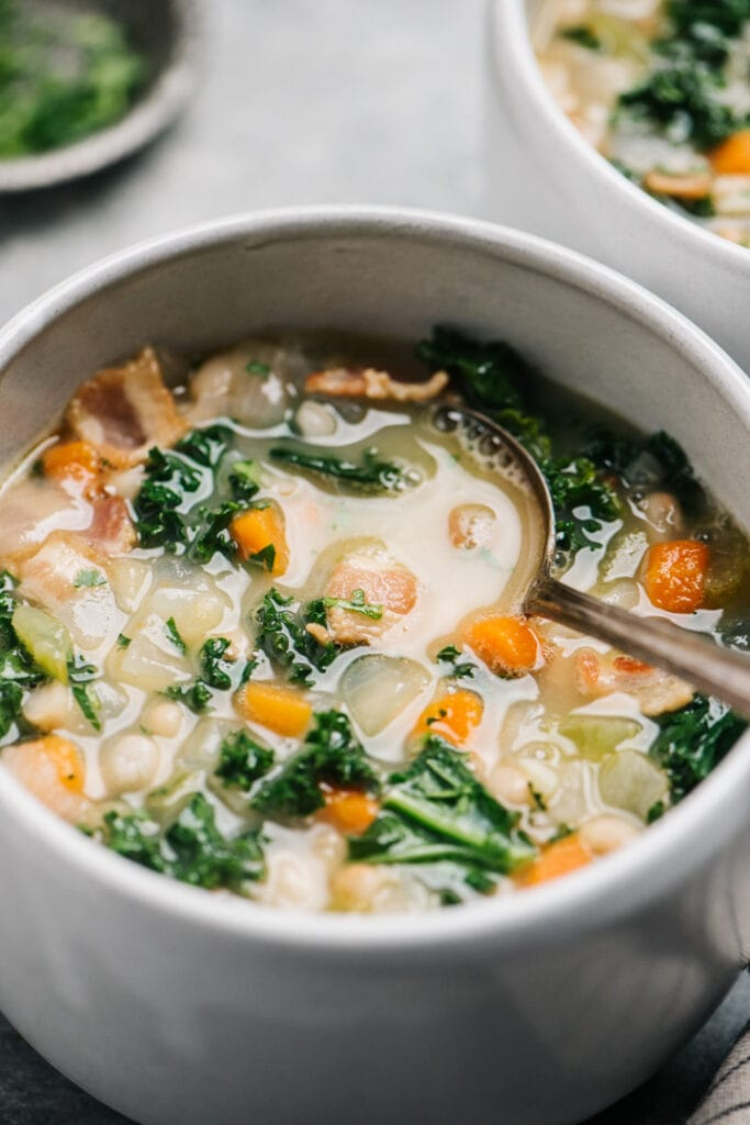 Side view, white bean and kale soup in a white bowl on a concrete background.