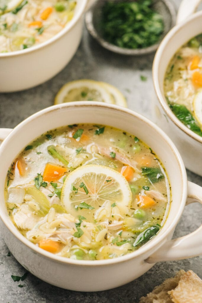 Side view, three bowls of lemon chicken orzo soup on a concrete background surrounded by lemon wheels, bread slices, and a small bowl of chopped parsley.