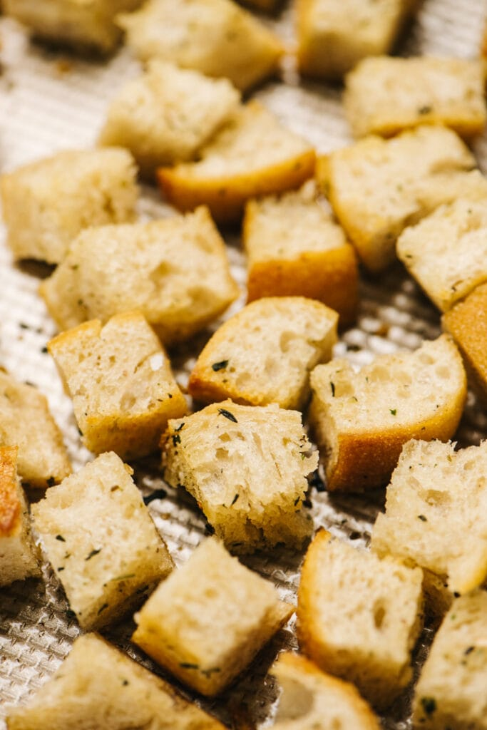 Side view, golden brown homemade croutons on a baking sheet.