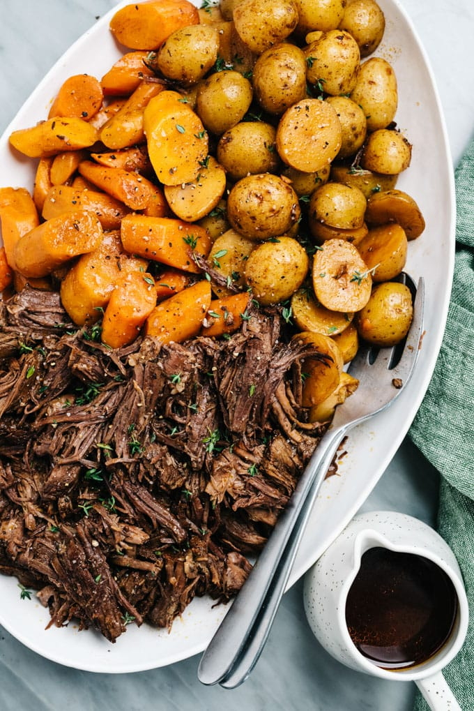 A platter of instant pot pot roast, potatoes, and carrots on a marble table with a green linen napkin and small pitcher of gravy.
