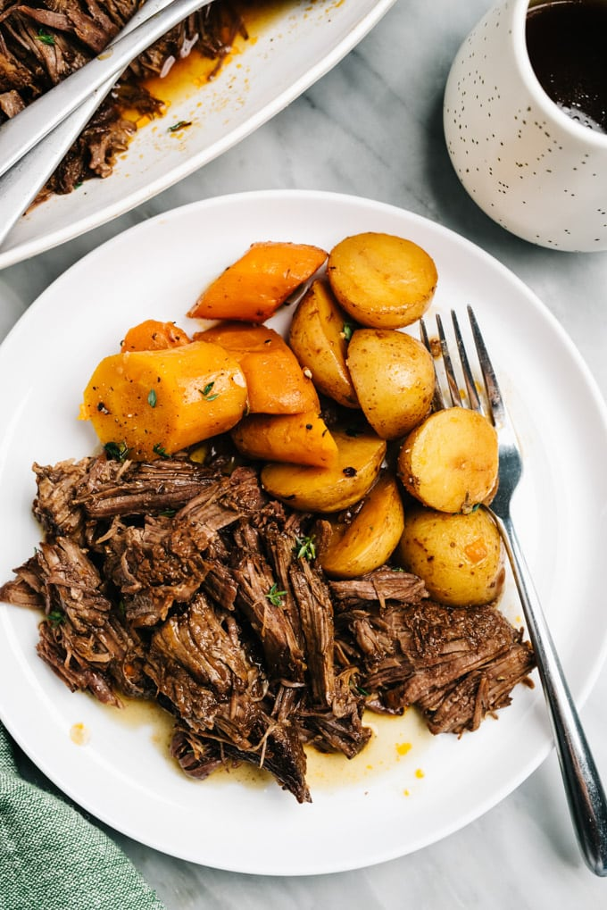 Shredded pot roast, potatoes, and carrots on a white plate with a silver fork and green napkin on a marble table.