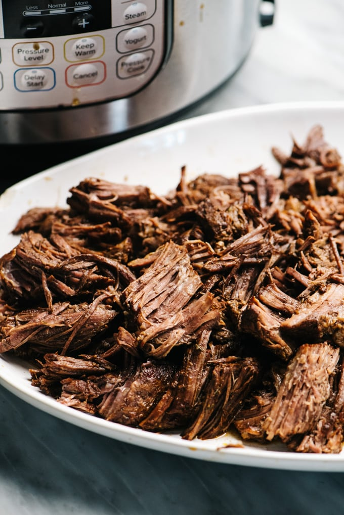 Side view, shredded chuck roast on a white platter with an instant pot in the background.