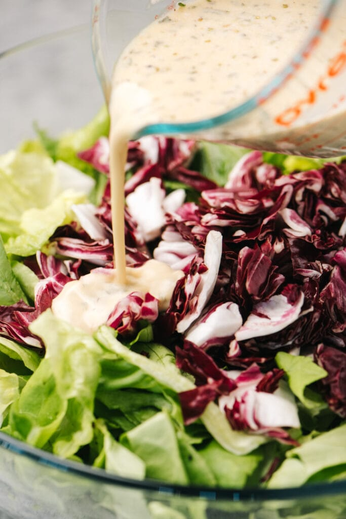 Pouring creamy italian dressing over chopped romaine lettuce and chopped radicchio.