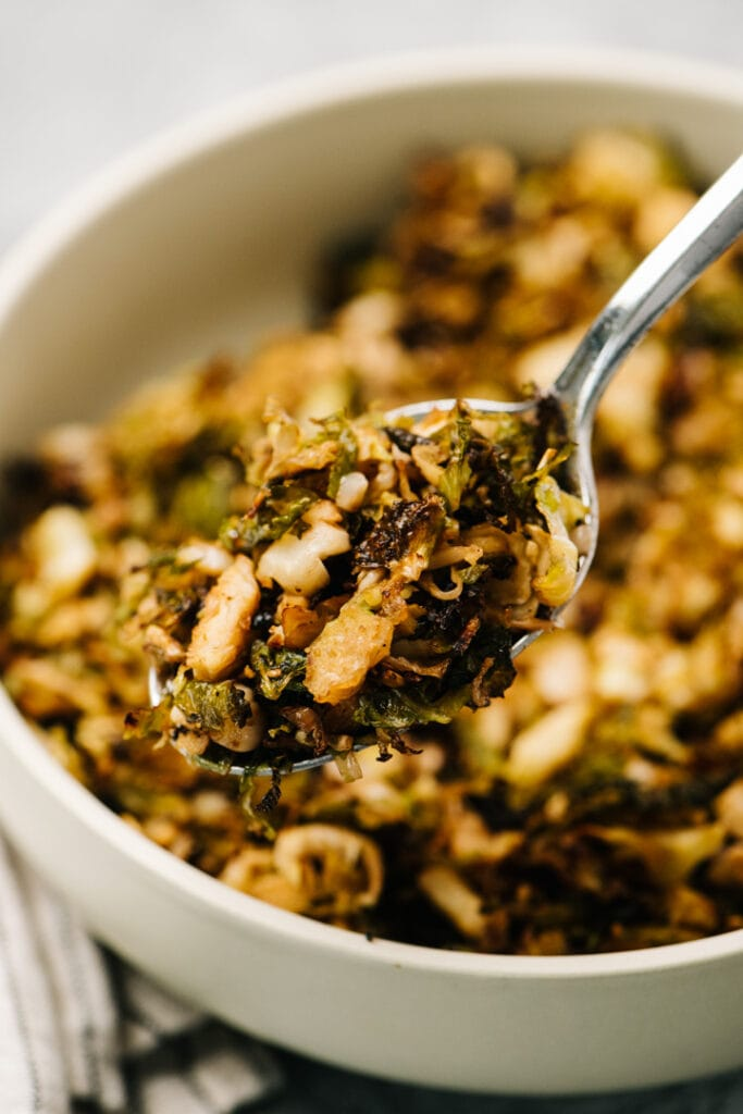 A spoonful of roasted shredded brussels sprouts hovering over a serving dish.