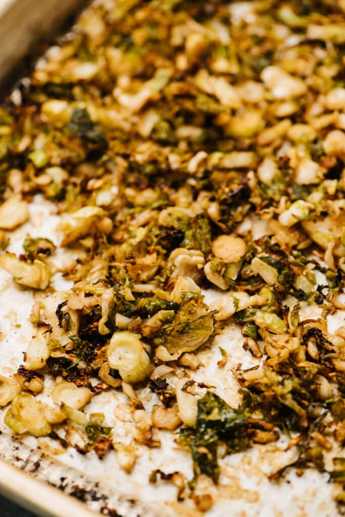 Side view, roasted shredded brussels sprouts on a parchment lined baking sheet.
