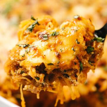 A spoonful of spaghetti squash lasagna hovering over a casserole dish.