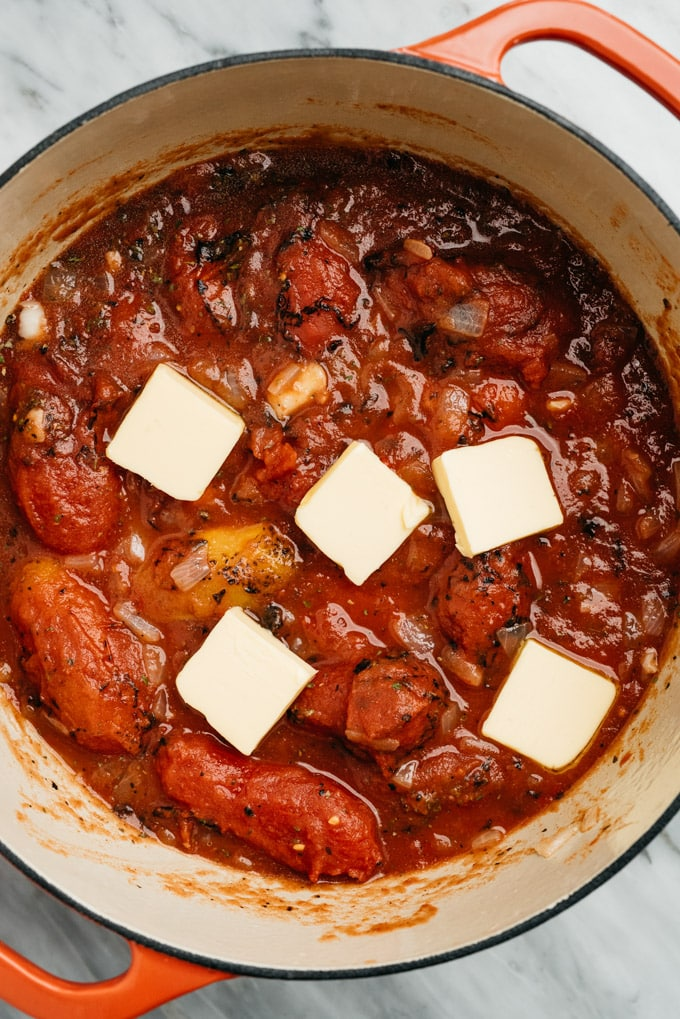 Five tablespoons of butter place on top of fire roasted tomatoes, herbs, and sautéed onions and garlic.