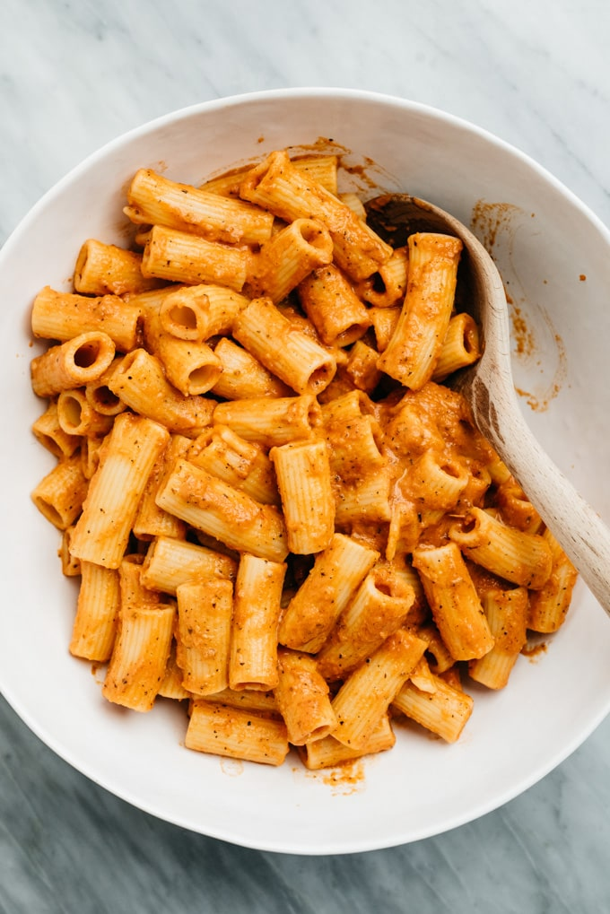Easy creamy tomato sauce tossed with rigatoni pasta in a white serving bowl.